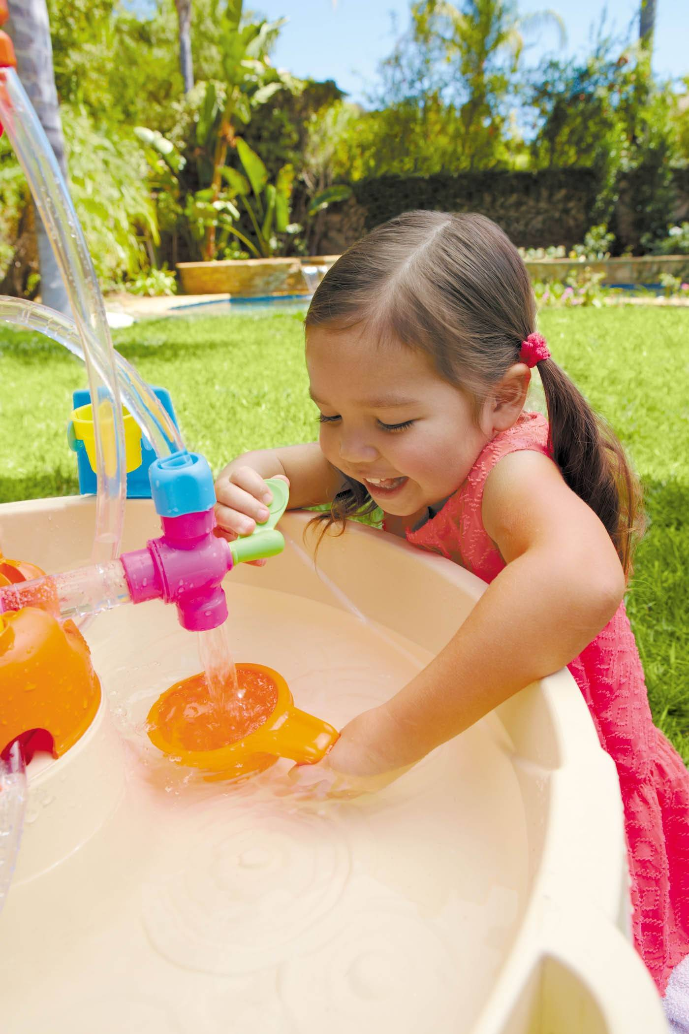 Dziecko bawi się wodnym stołem fabryką fontann little tikes